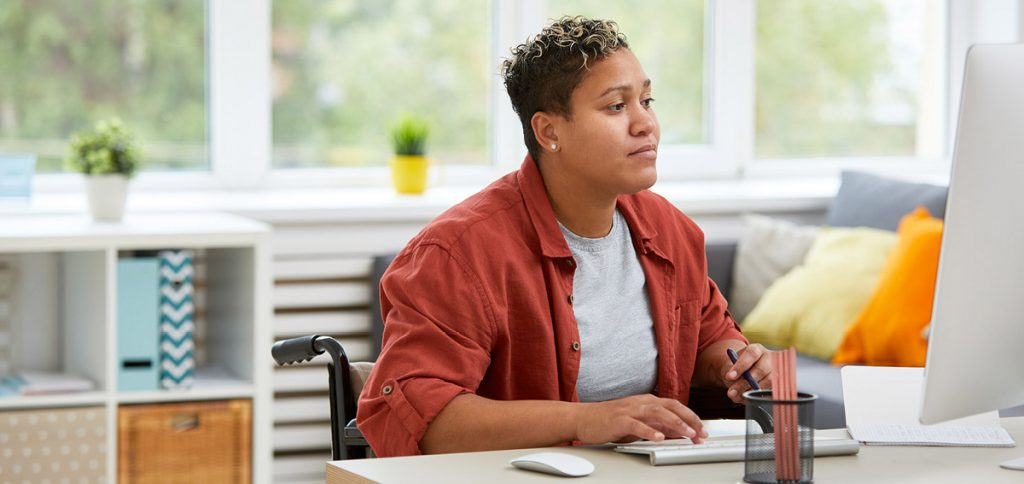 Middle-aged Black woman is sitting at a work desk in a wheelchair, working on her office computer