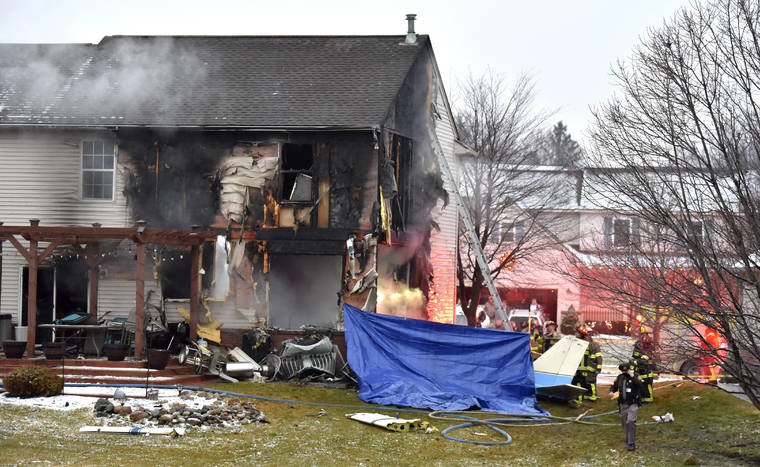 ASSOCIATED PRESS First responders investigate the scene of a plane that crashed into a house, setting it on fire in Lyon Township, Michigan Saturday night.