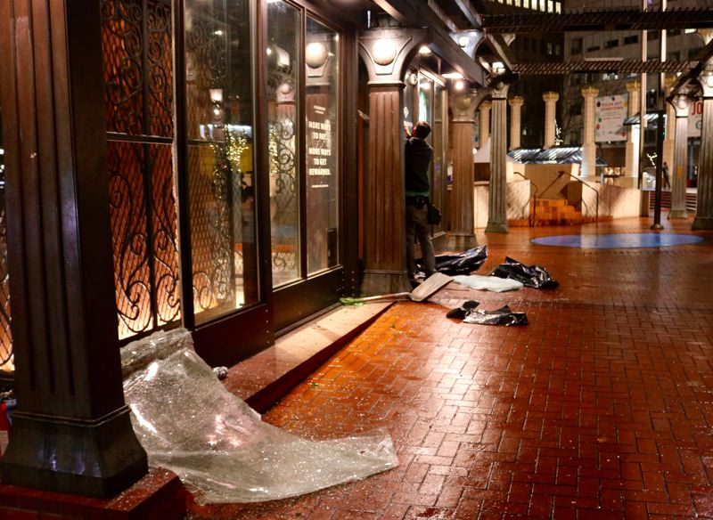 PMG PHOTO: ZANE SPARLING - A worker repairs damage to the Starbucks coffee shop at Pioneer Courthouse Square in downtown Portland on Jan. 1.
