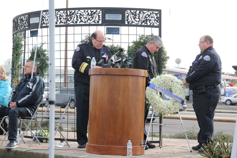 PMG PHOTO: PHIL HAWKINS - In 2018 Officer Craig Halupowski, right, and Officer Jorge Gaspar place a wreath on the memorial in memory of Capt. Tom Tennant, who died in a Woodburn West Coast Bank bombing. Chief Jim Ferraris looks on.